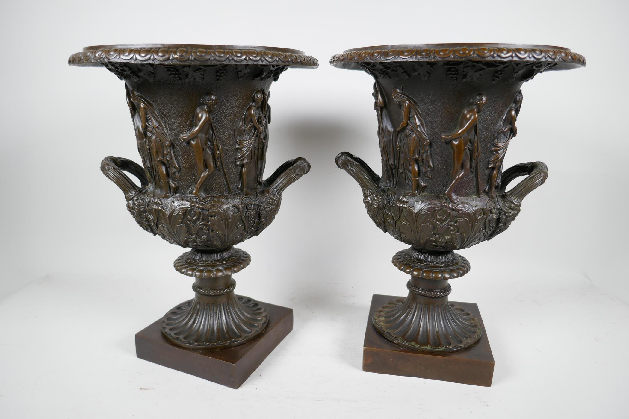 A pair of classical Grand Tour style bronze pedestal urns decorated with many figures on square