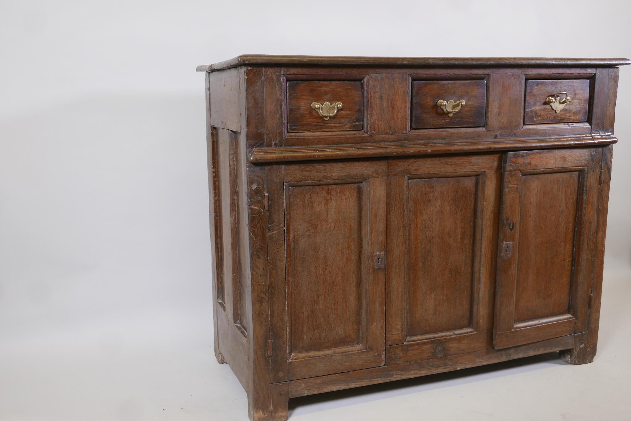 An antique oak side cabinet, with panelled ends and cupboards under three drawers, C18th and later - Image 2 of 5