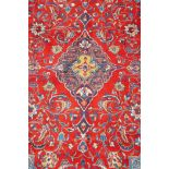 """A full pile fine woven Sarouk carpet with a floral medallion design on a red field, 112"""" x 78"""""""