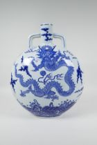 A Chinese blue and white porcelain moon flask decorated with a dragon chasing the flaming pearl,