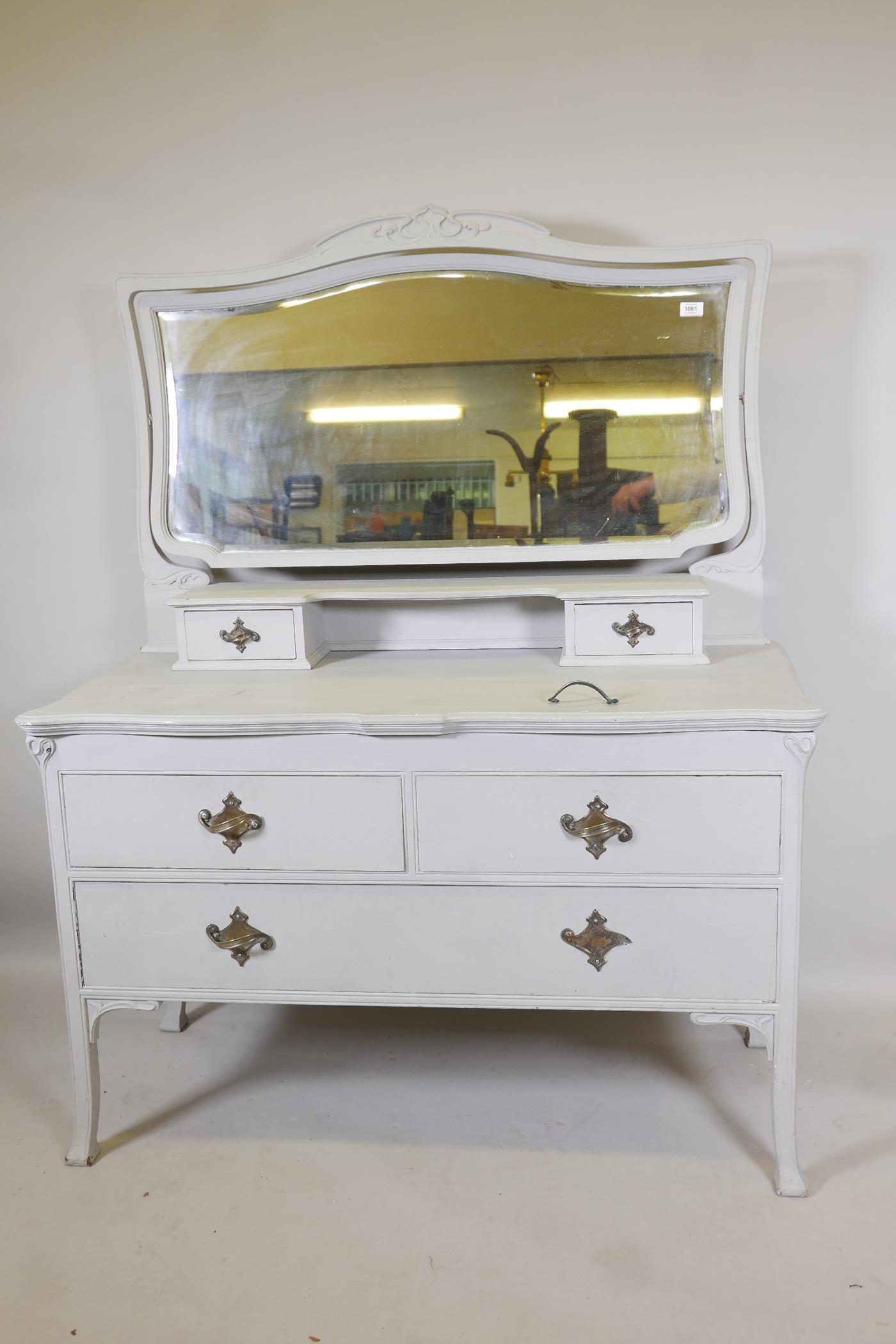 An Edwardian painted dressing table, with carved details, the mirrored top section with two drawers,