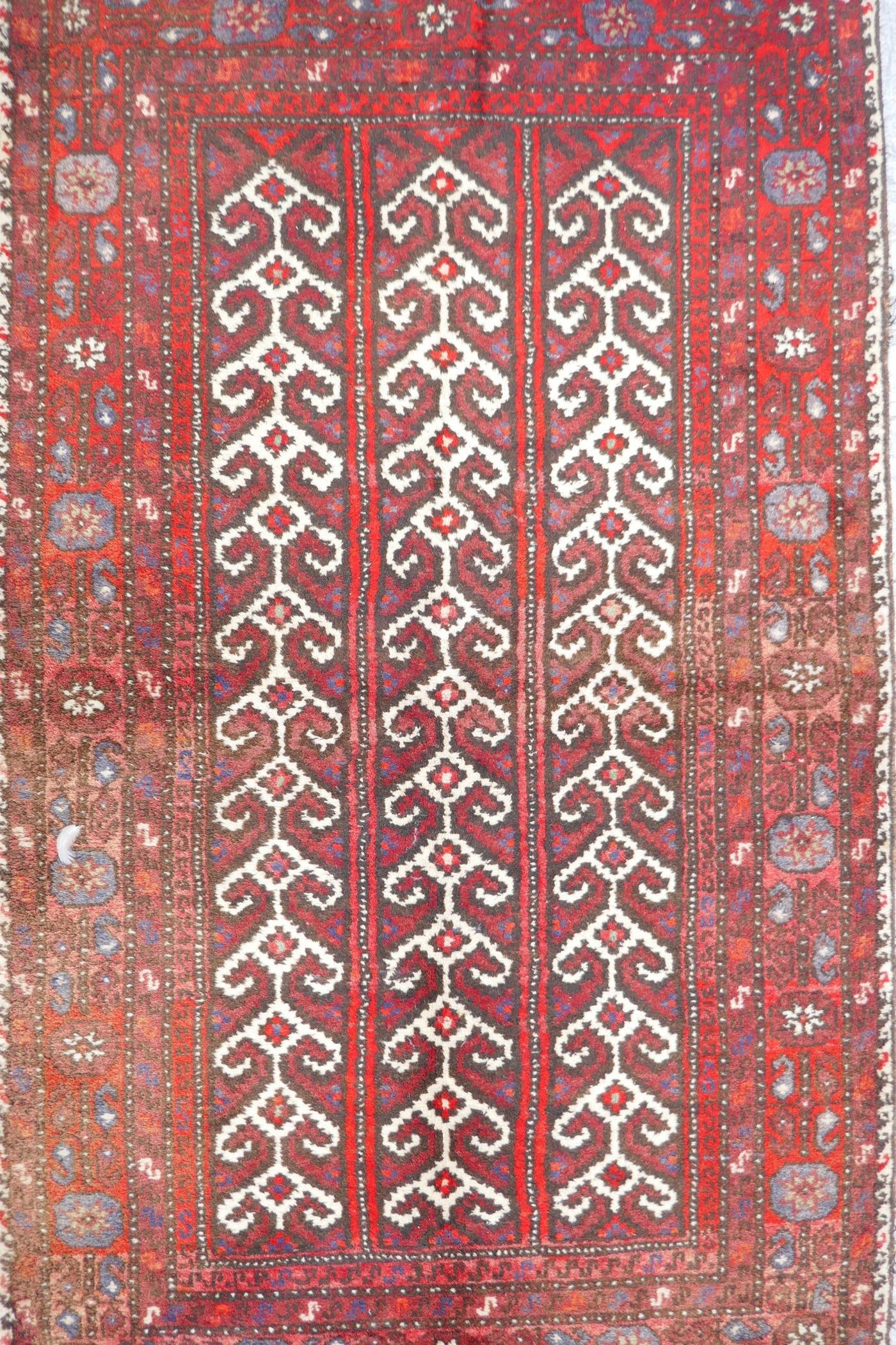 """A Middle Eastern full pile red ground wool rug with a three panel geometric design, 34"""" x 56"""""""