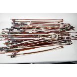 A box containing over fifty violin bows, varying lengths, mostly for restoration
