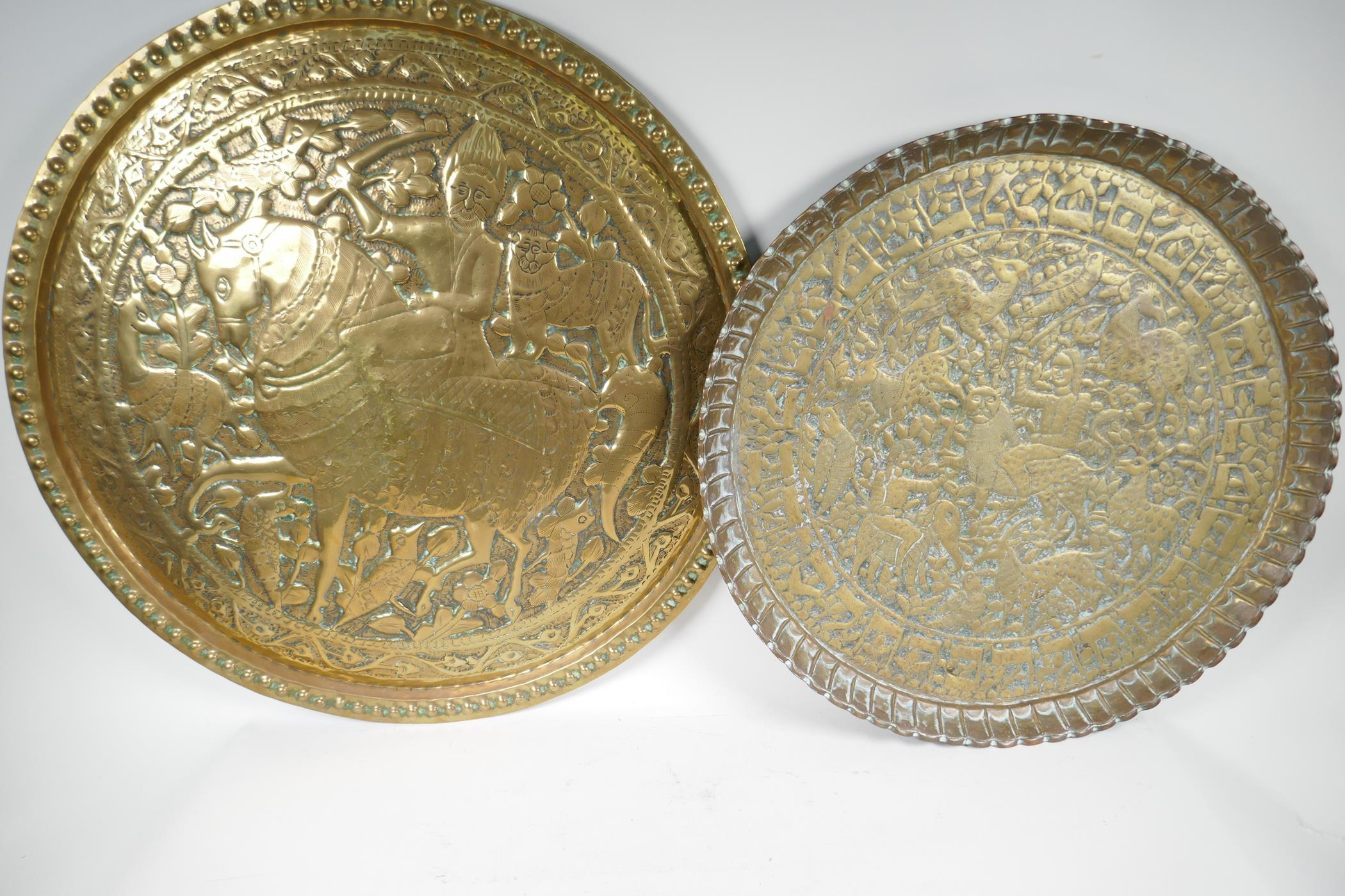 """A Persian brass charger embossed with a figure on horseback surrounded by animals and birds, 24"""""""