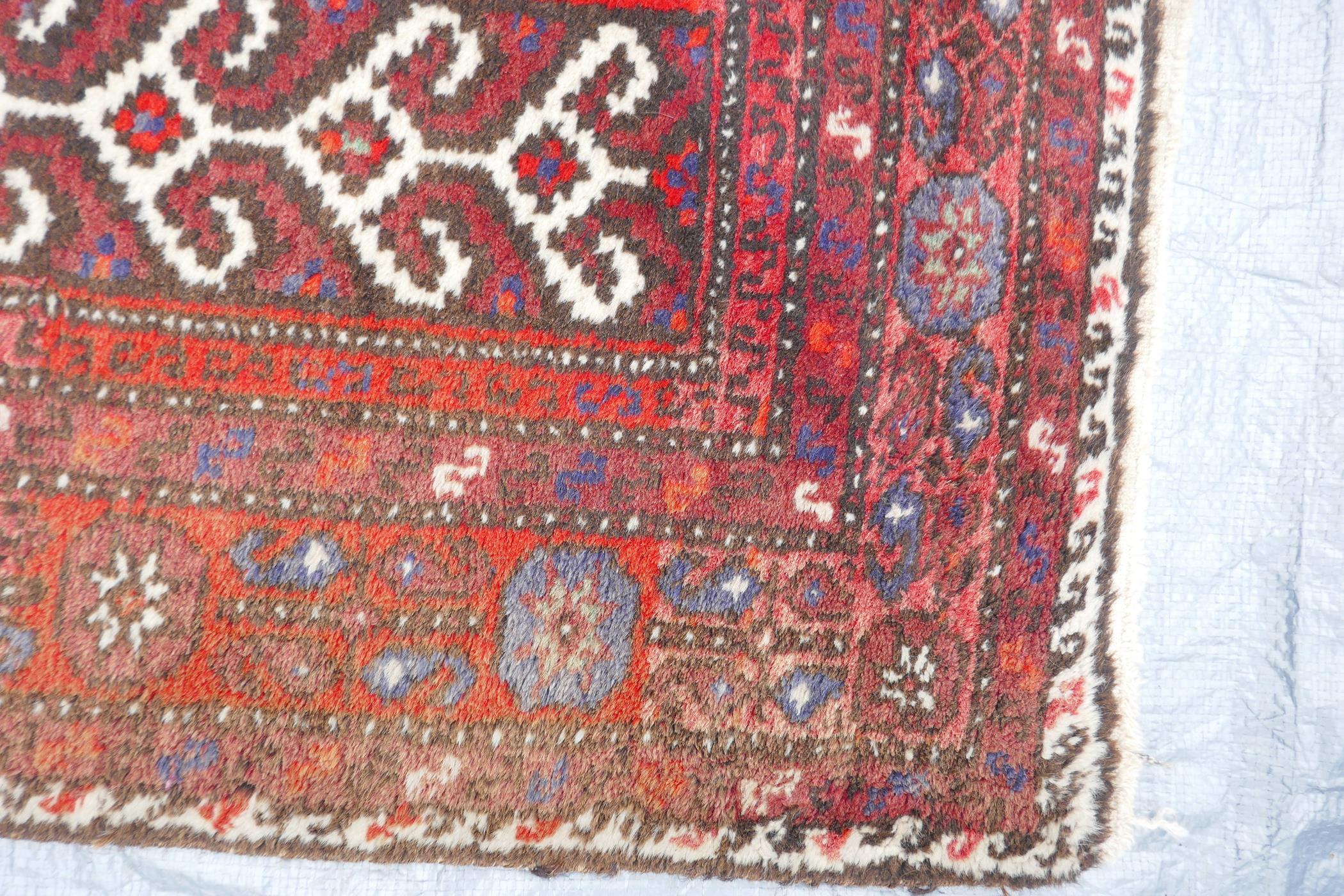 """A Middle Eastern full pile red ground wool rug with a three panel geometric design, 34"""" x 56"""" - Image 3 of 4"""