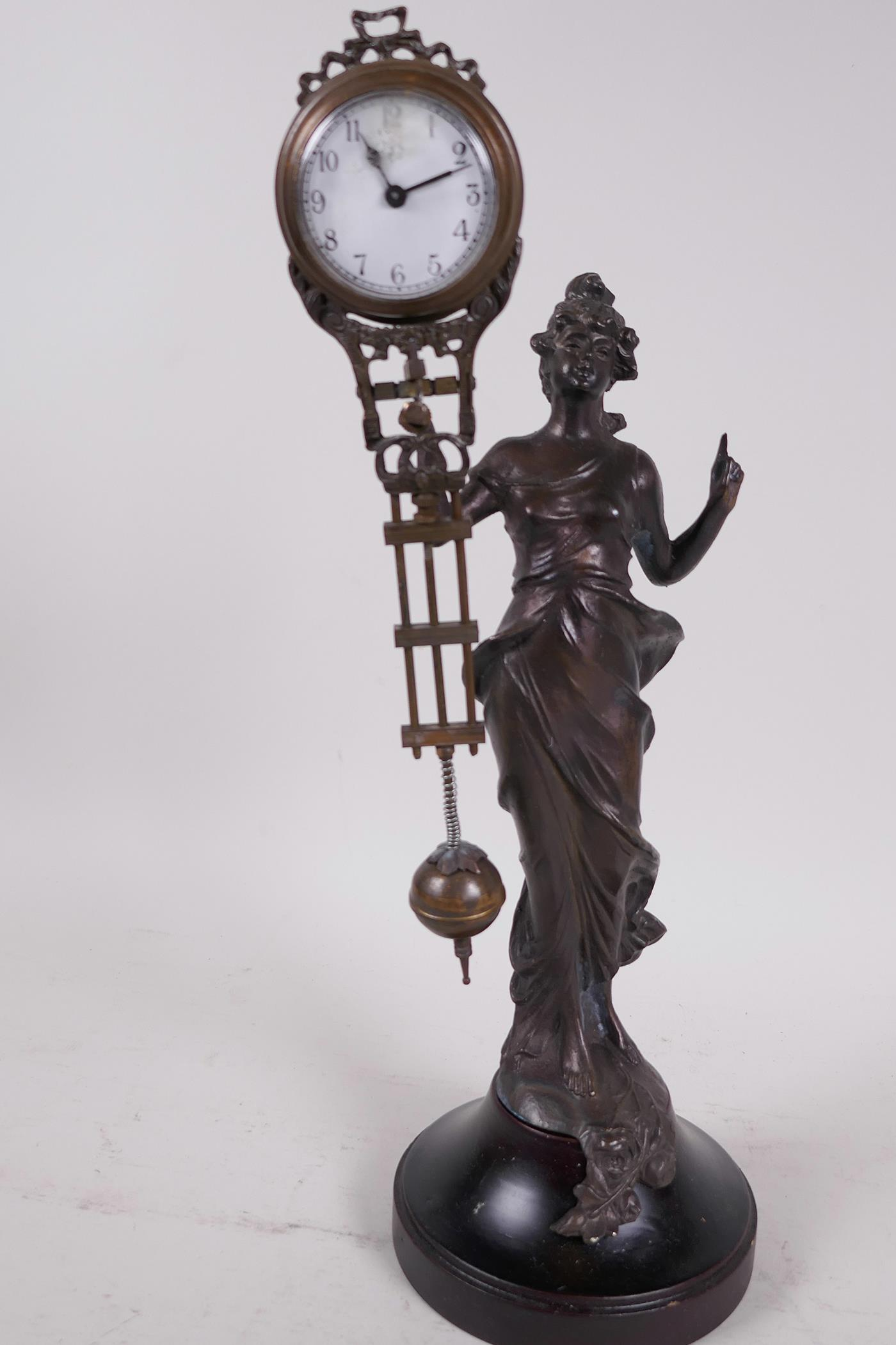 """A bronze mystery clock cast as an Art Nouveau style lady with the clock raised on one arm, 13"""" high"""