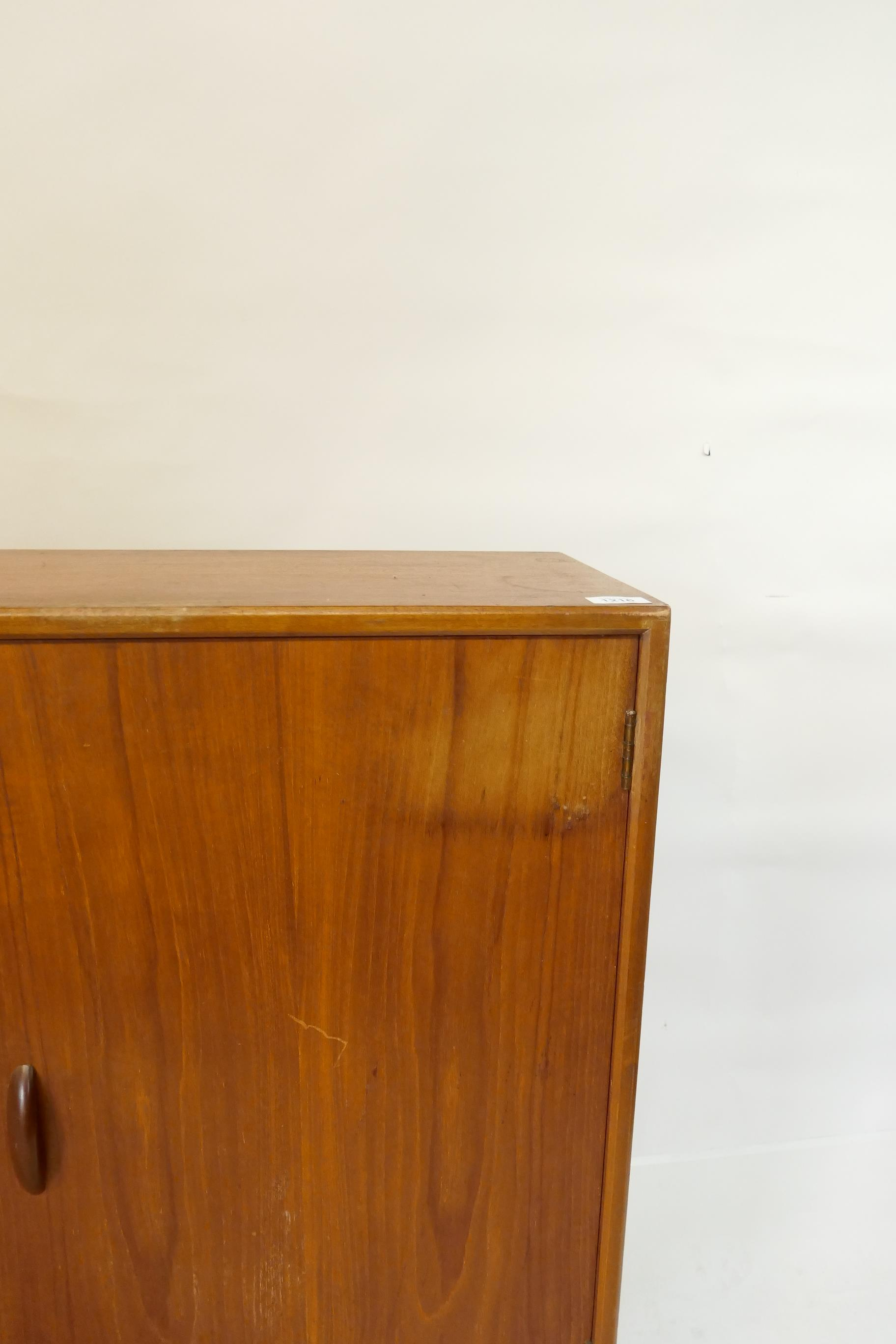A mid C20th teak side cabinet with single door and two sliding glass doors, bears label Herbert E. - Image 3 of 3