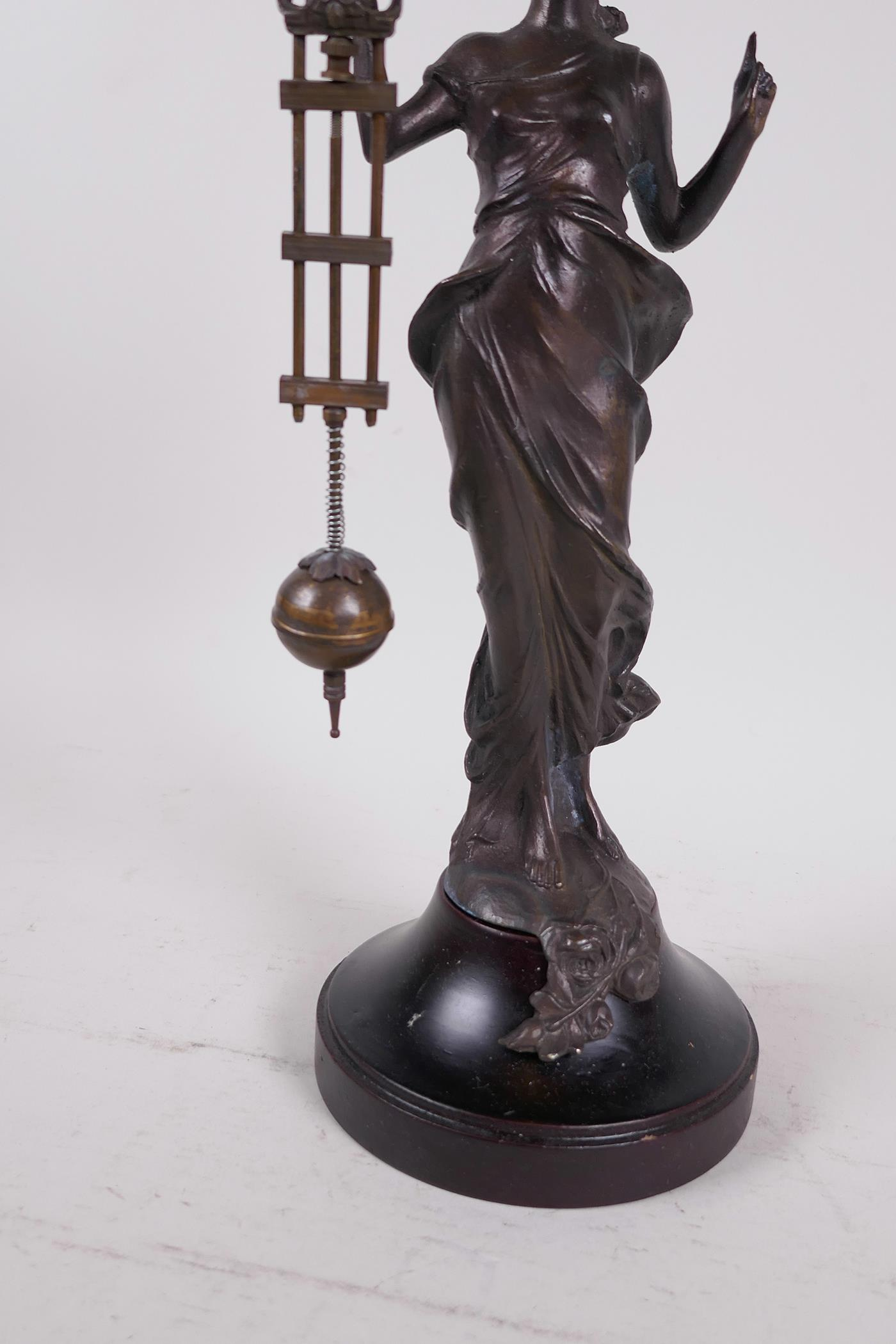 """A bronze mystery clock cast as an Art Nouveau style lady with the clock raised on one arm, 13"""" high - Image 4 of 4"""