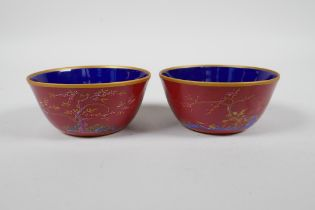 A pair of Chinese red ground porcelain tea bowls with polychrome decoration of flowers, foliage