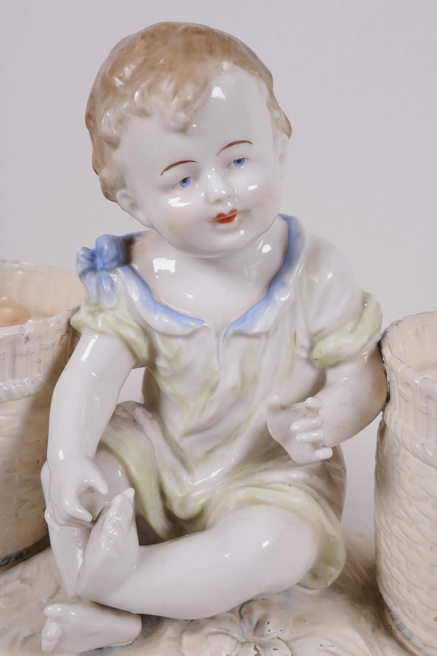 """A decorative porcelain planter in the form of a young girl seated between two large baskets, 11½"""" - Image 2 of 3"""
