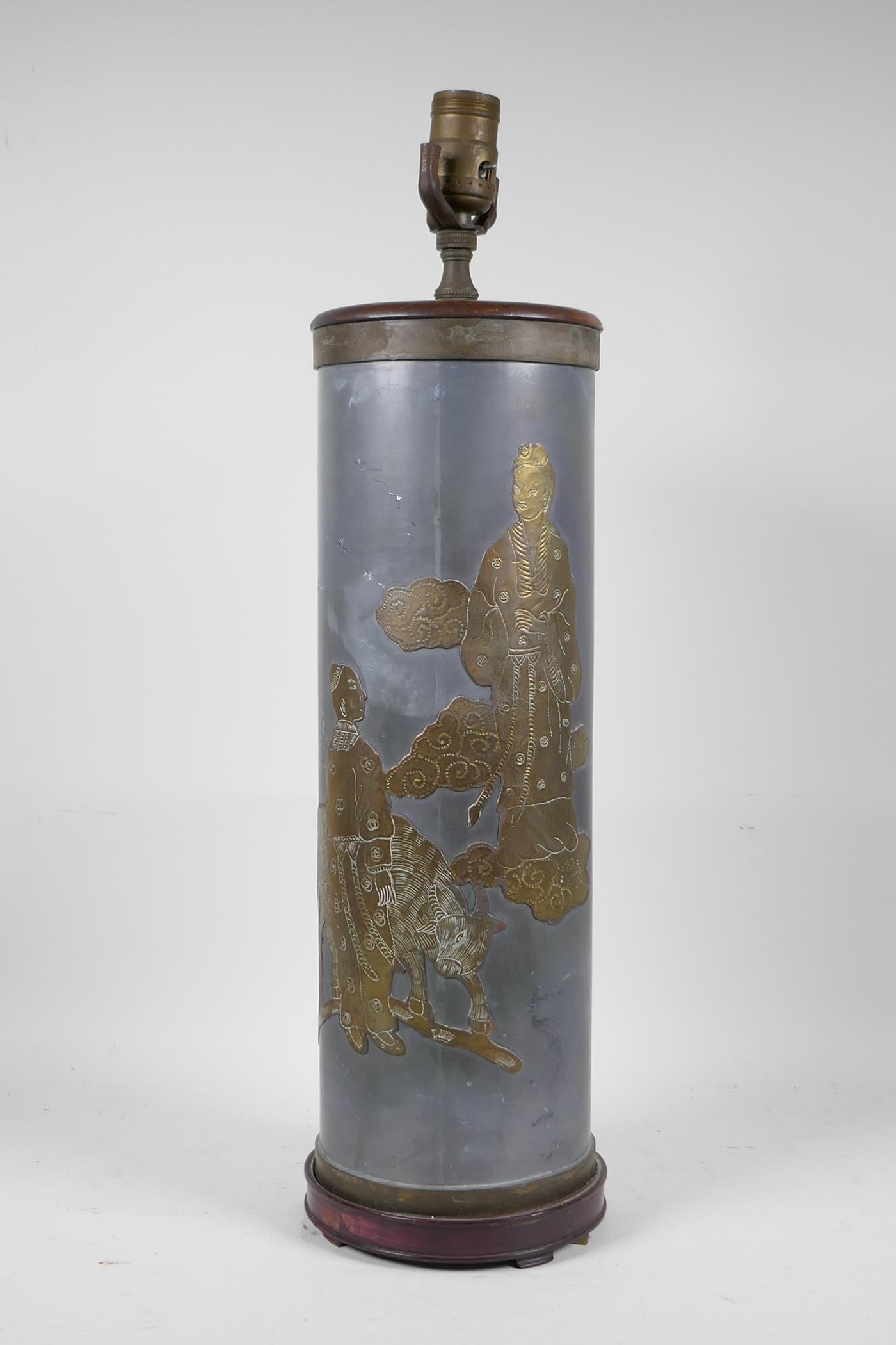 """A pewter and brass cylinder lamp with Chinese decoration depicting figures and a buffalo, 21"""" high"""
