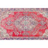 A vintage Iranian carpet from the Tabriz region, with floral medallion design on a red field with