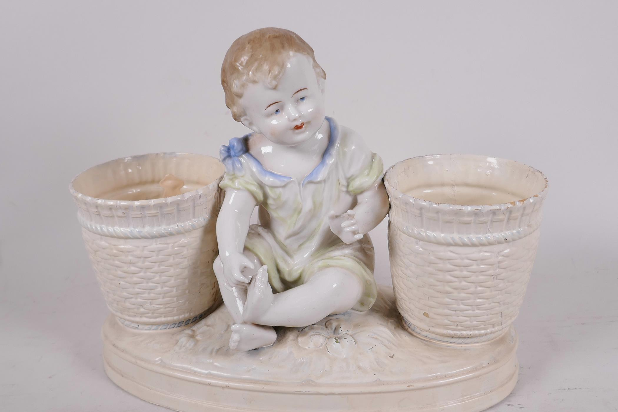 """A decorative porcelain planter in the form of a young girl seated between two large baskets, 11½"""""""