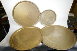 """Four Islamic brass trays, all with engraved decoration, largest 26"""" diameter"""