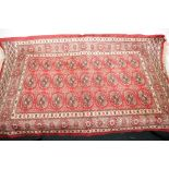 """A small Bokhara pattern red ground rug, 44"""" x 26"""""""