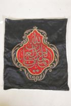 """An Islamic wall hanging embroidered with calligraphy in gilt metal wire on a red ground, 32"""" x 27"""""""