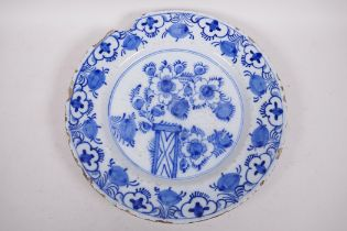 """An antique Delft tin glazed blue and white charger painted with flowers and fruit, chip to rim, 13½"""""""