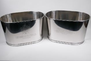 A pair of large plated metal champagne coolers, engraved with aphorisms from Lily Bolinger and