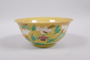 A Chinese yellow ground porcelain rice bowl decorated with red crowned cranes in flight, 6 character