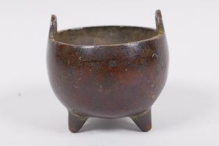 A miniature Chinese bronze cauldron shaped censer with two loop handles and three cast feet,