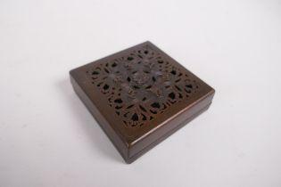 A sino Tibetan bronze incense box and pierced cover, decorated with auspicious symbols, impressed