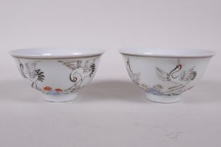 A pair of early C20th Chinese polychrome porcelain tea bowls decorated with cranes, seal mark to
