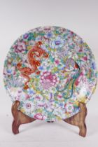 A Chinese porcelain charger painted in bright enamels with a dragon and phoenix on a mille fleur