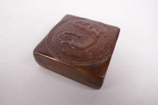 A bronzed copper ink box with repousse dragon decoration to the cover, impressed mark to base,