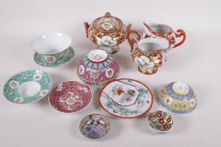 A Noritake porcelain two handled sucrier and cover, painted with flowers and a matching cream jug,