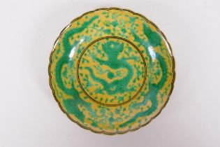 A Chinese yellow ground porcelain saucer with a shaped rim and green dragon decoration, Qian long