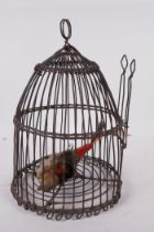 """A domed wire bird cage with woven banding, housing a model bird with metal head and feet, 11"""" high"""