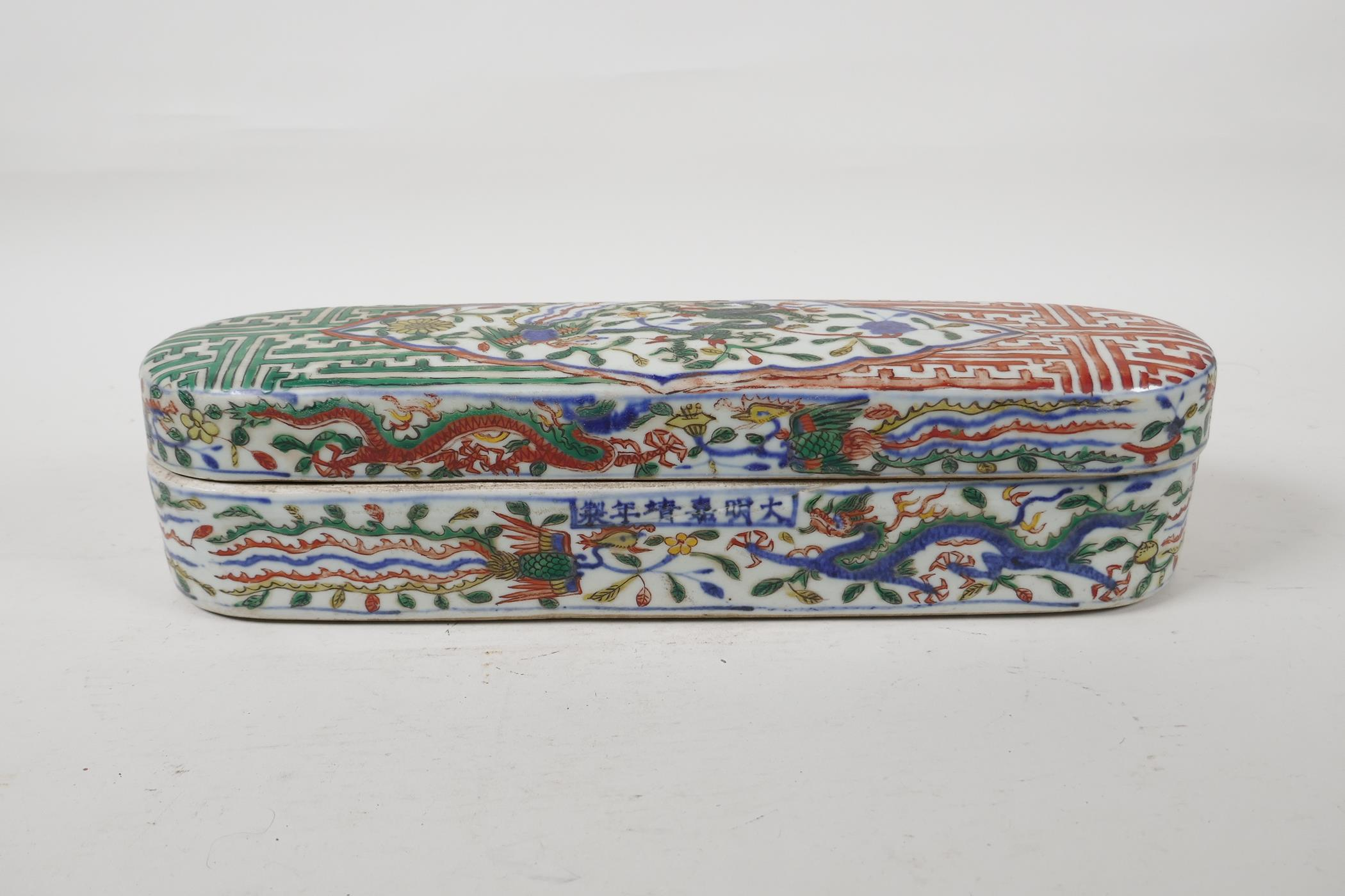 A wucai porcelain scribes box with dragon and phoenix decoration, six character mark to side,