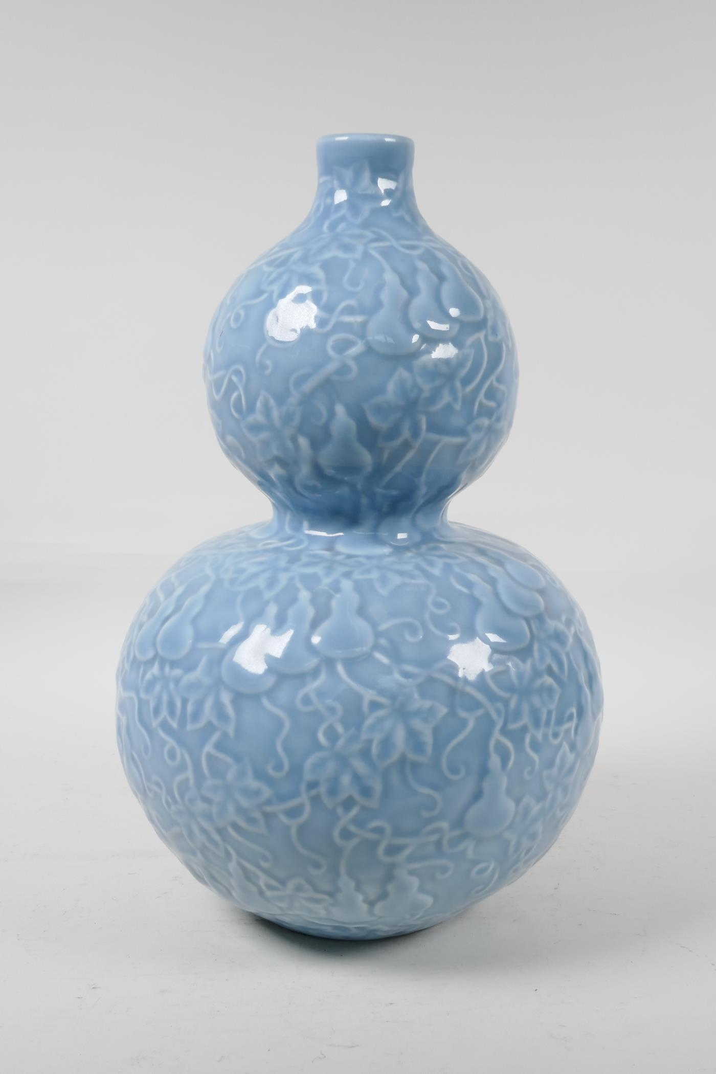 A Chinese blue glazed porcelain double gourd vase, with all over raised gourd vine decoration,