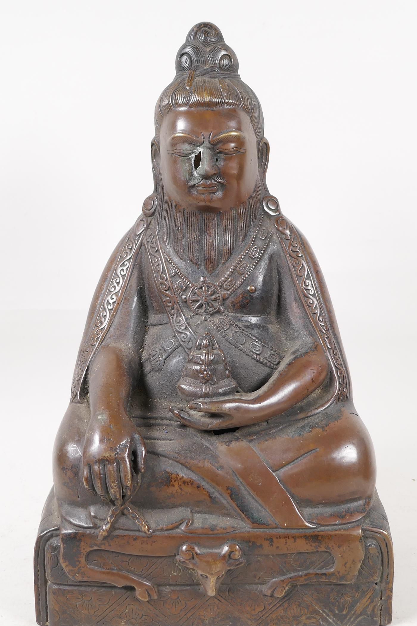 "A Sino Tibetan bronze figure of a deity seated in meditation, 11½"" high"