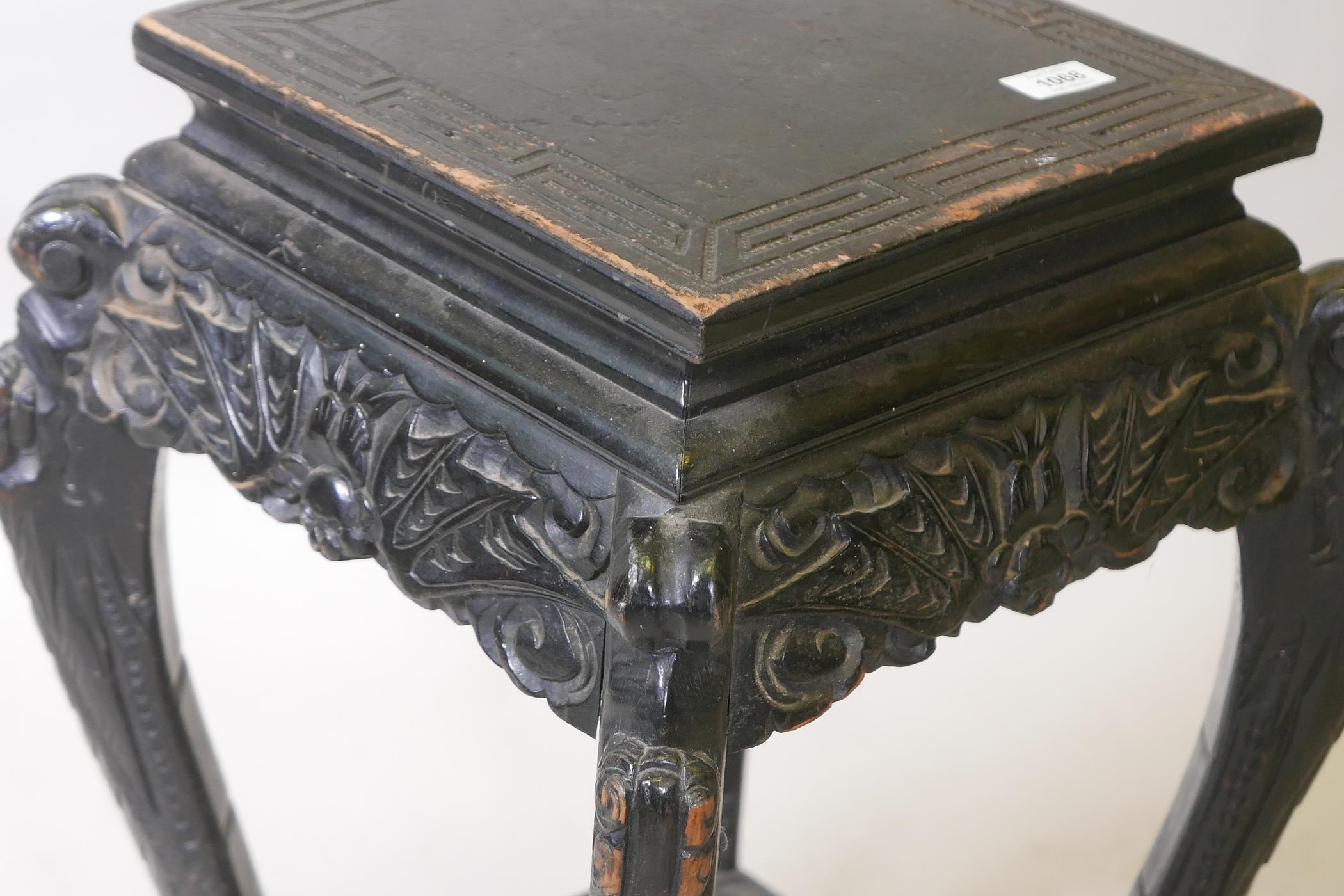 A Chinese two tier ebonised wood stand, with carved bat frieze, raised on scrolled shaped - Image 2 of 3