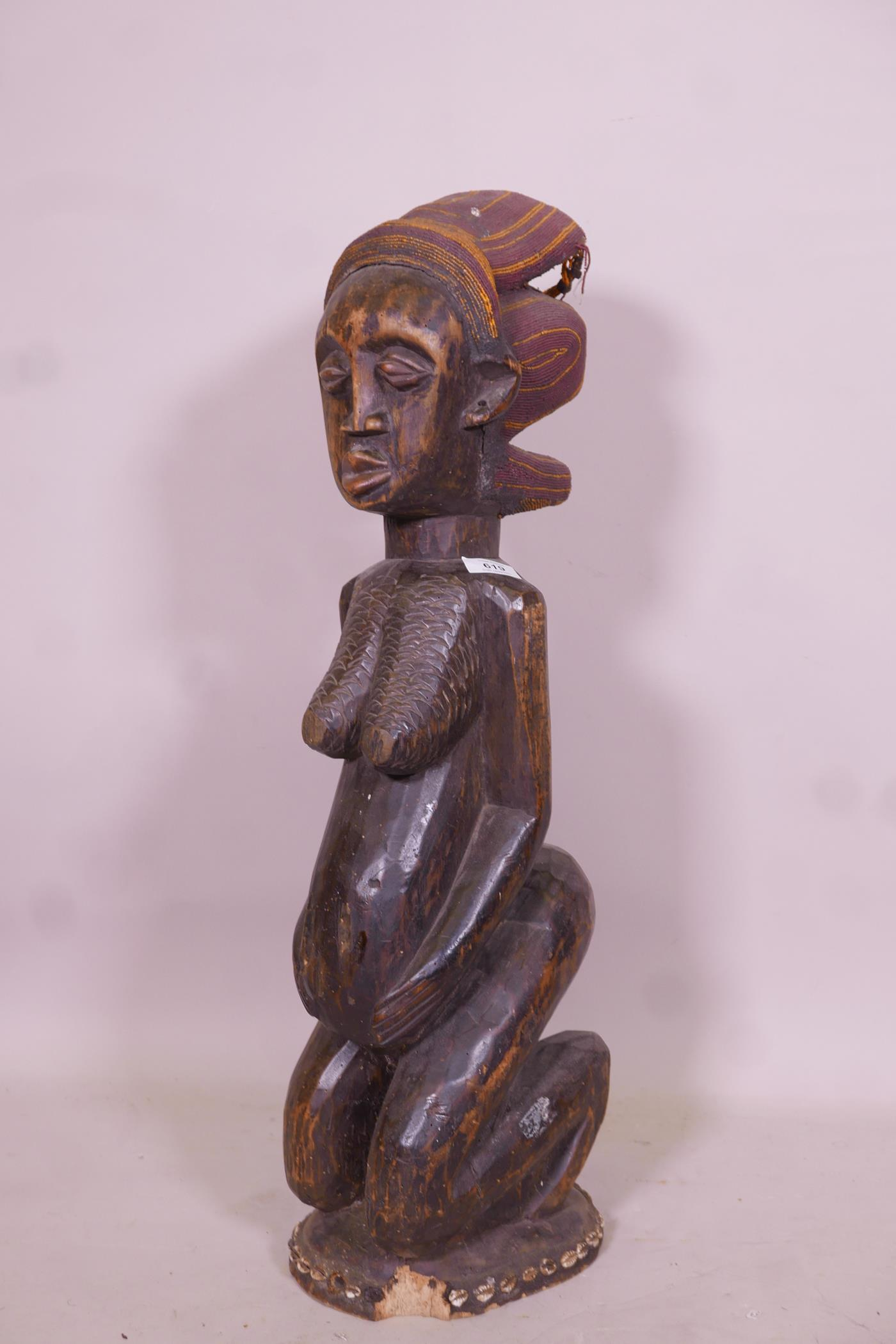An antique African carved wood fertility figure with beaded headdress and inset with sea shells,