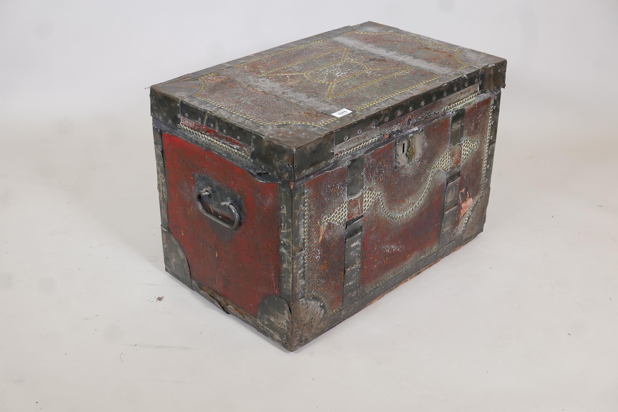 An early C19th painted leather trunk with brass stud decoration and steel straps, original papered