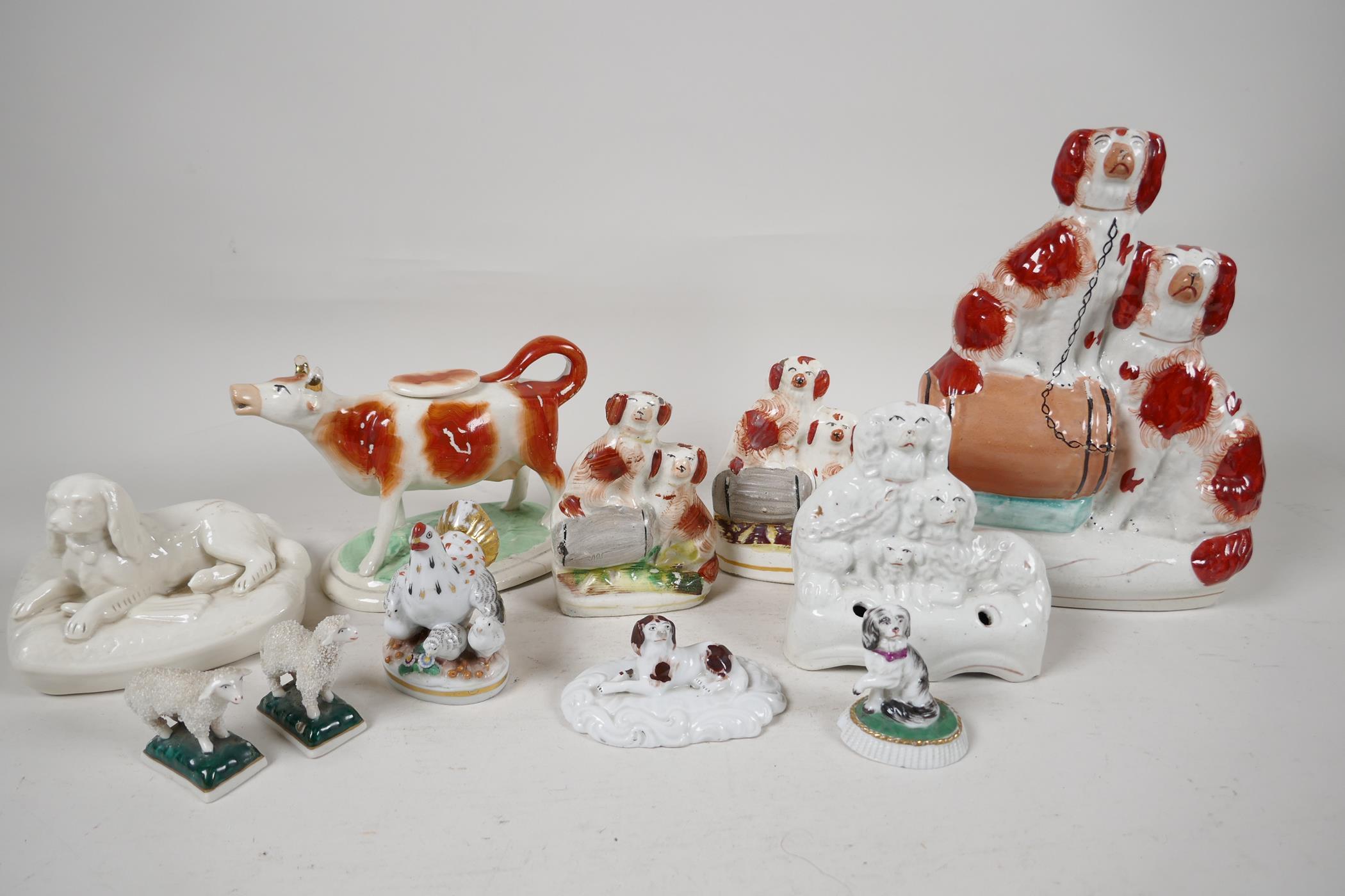 "Four Staffordshire flat back dog figures, largest 9"" high, a Staffordshire cow creamer, Beleek dog"