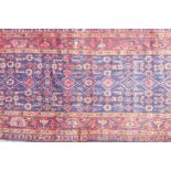 """A large blue ground hand woven Persian runner with an all over design within a red border, 44"""" x"""