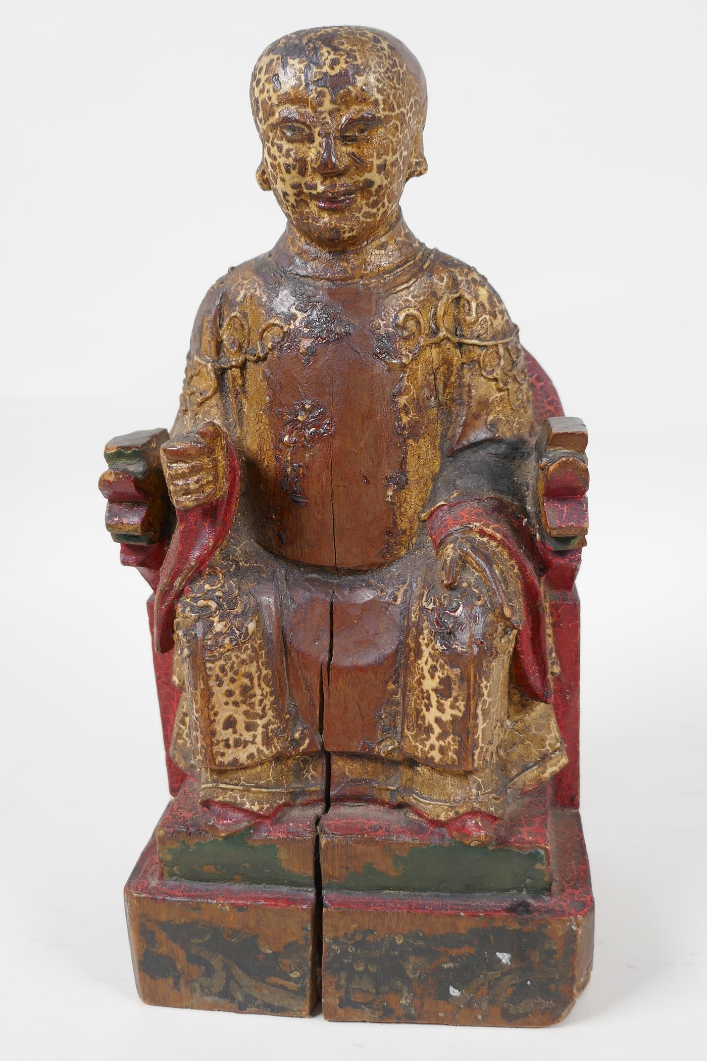 """A Chinese carved wood figure of a dignitary seated on a throne, traces of paint, 9"""" high"""