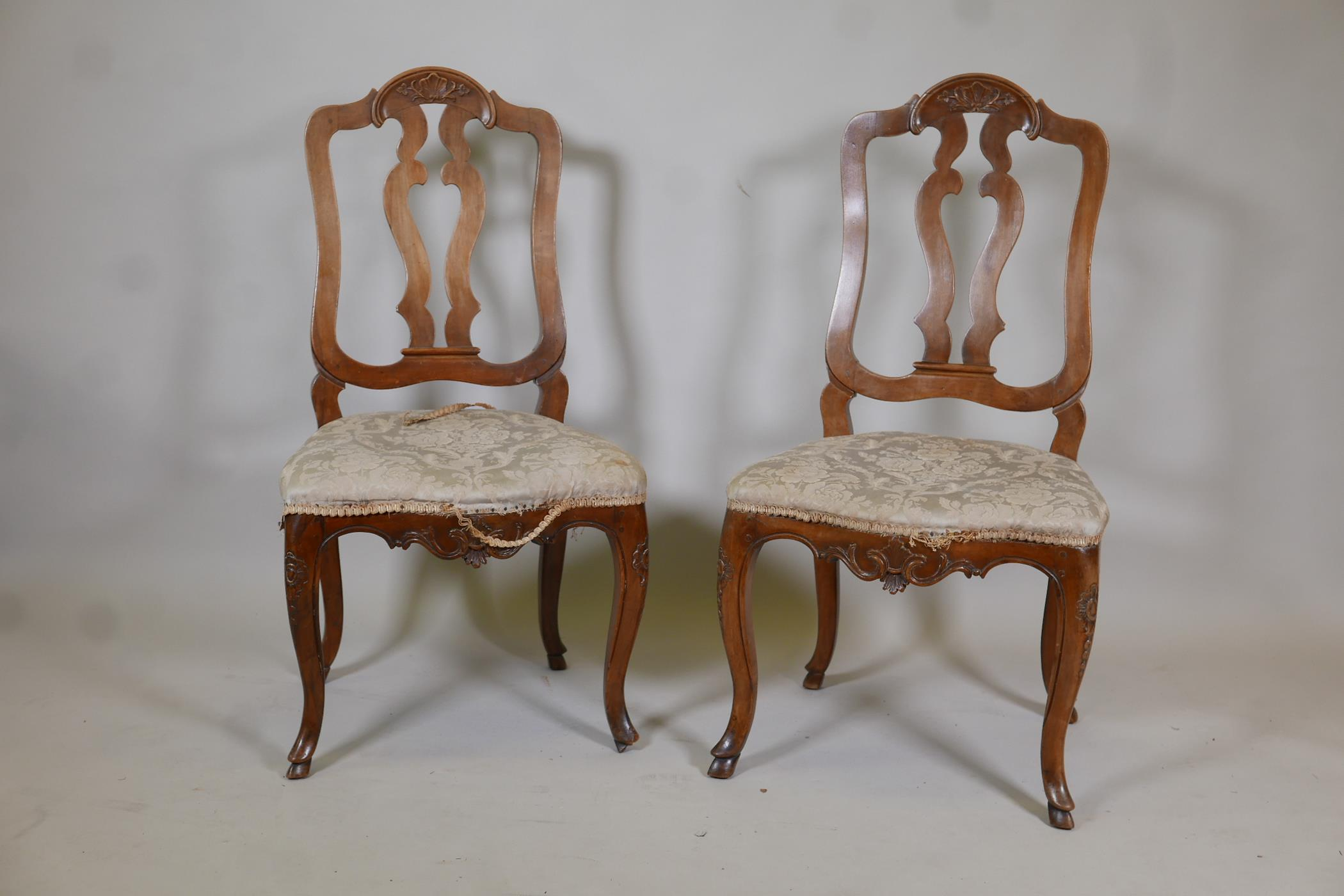 A pair of C18th French walnut pierced splat back side chairs with finely carved decoration, raised
