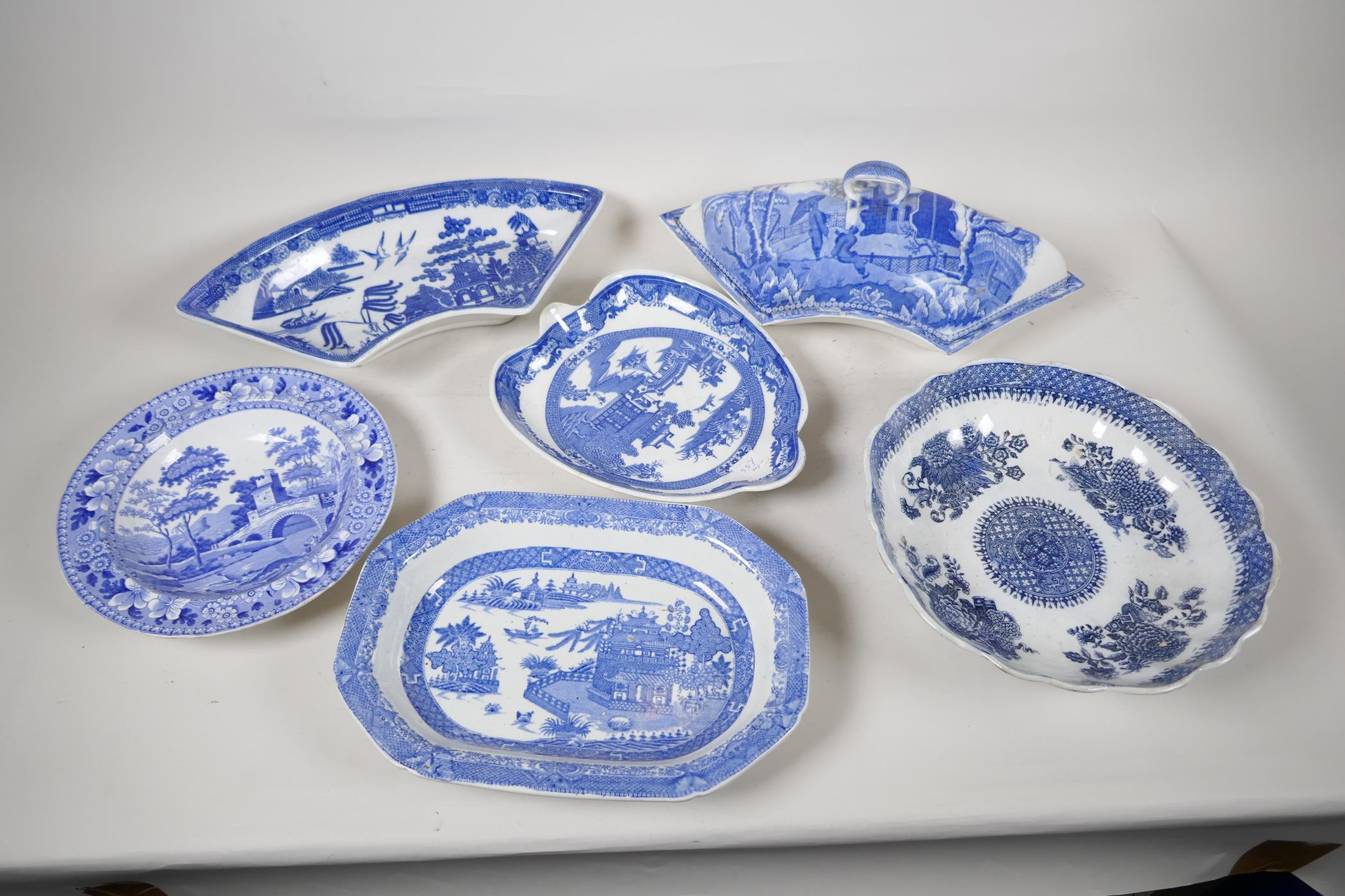 """A quantity of C19th blue and white pottery to include a crescent shaped tureen, 13"""" wide, a petal"""