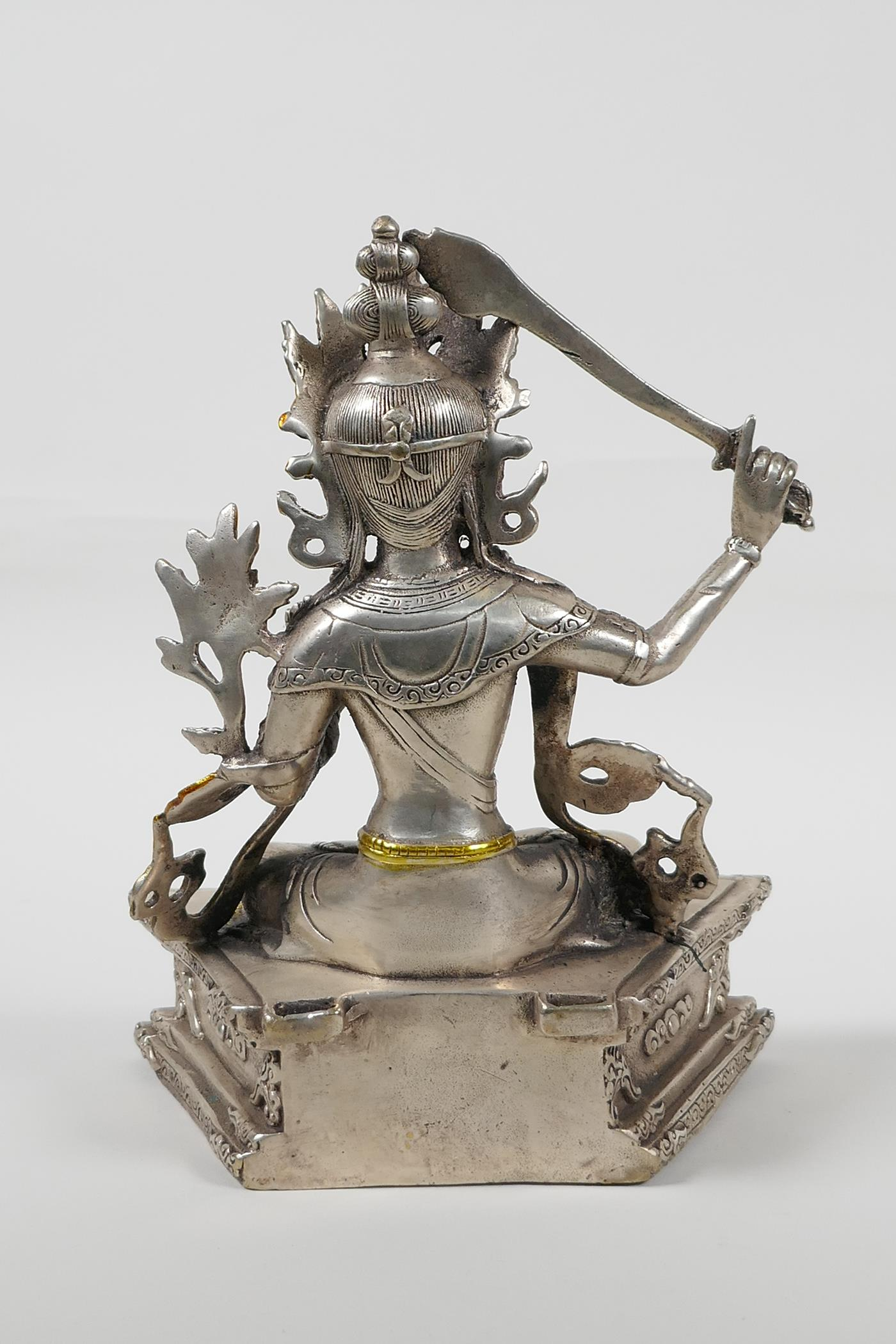 A Sino Tibetan white metal figure of a seated deity carrying a sword with gilt highlights, double - Image 4 of 5