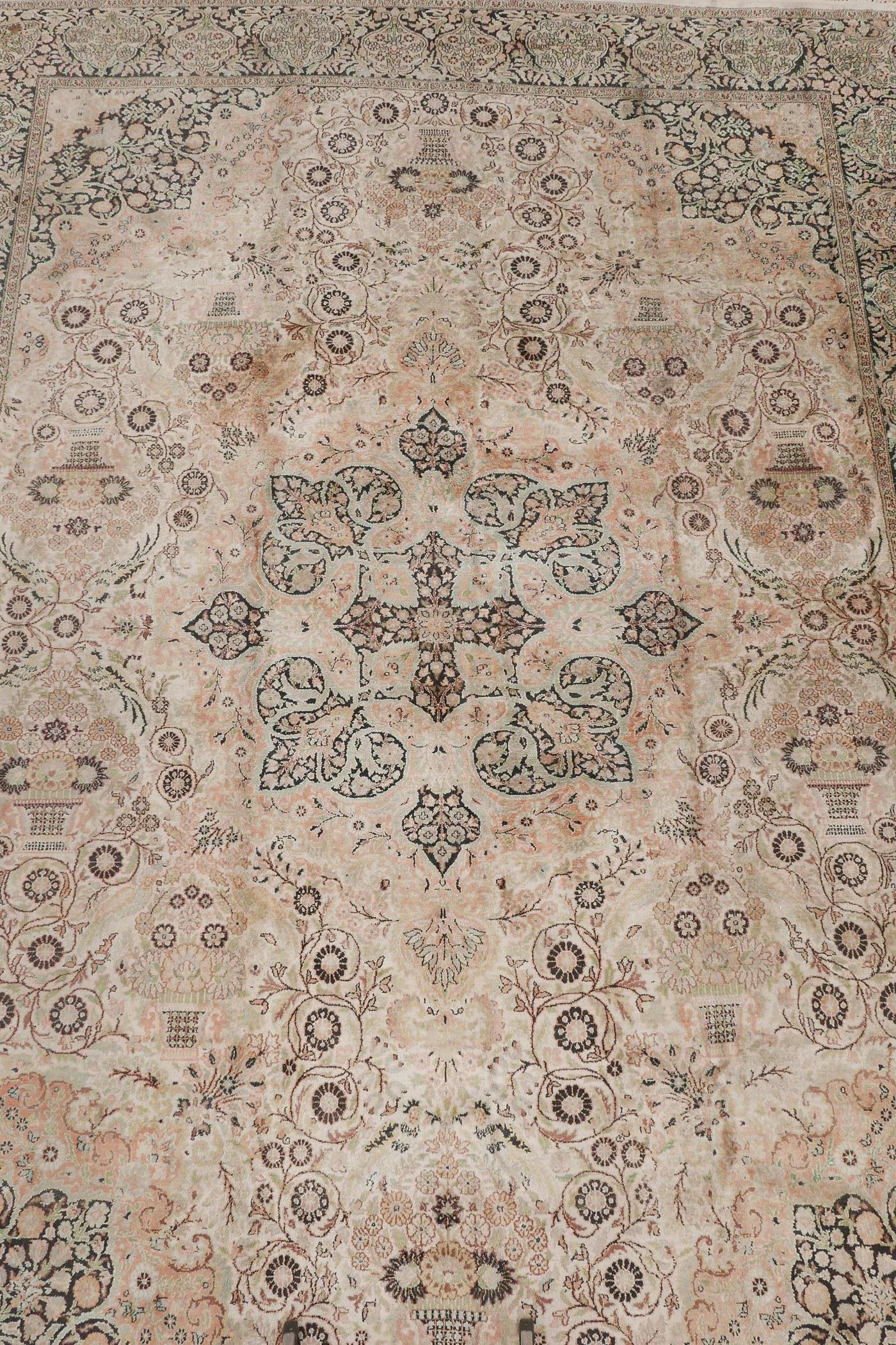 """An oriental ivory ground silk carpet, with multicolour floral decoration within a black border, 151"""""""