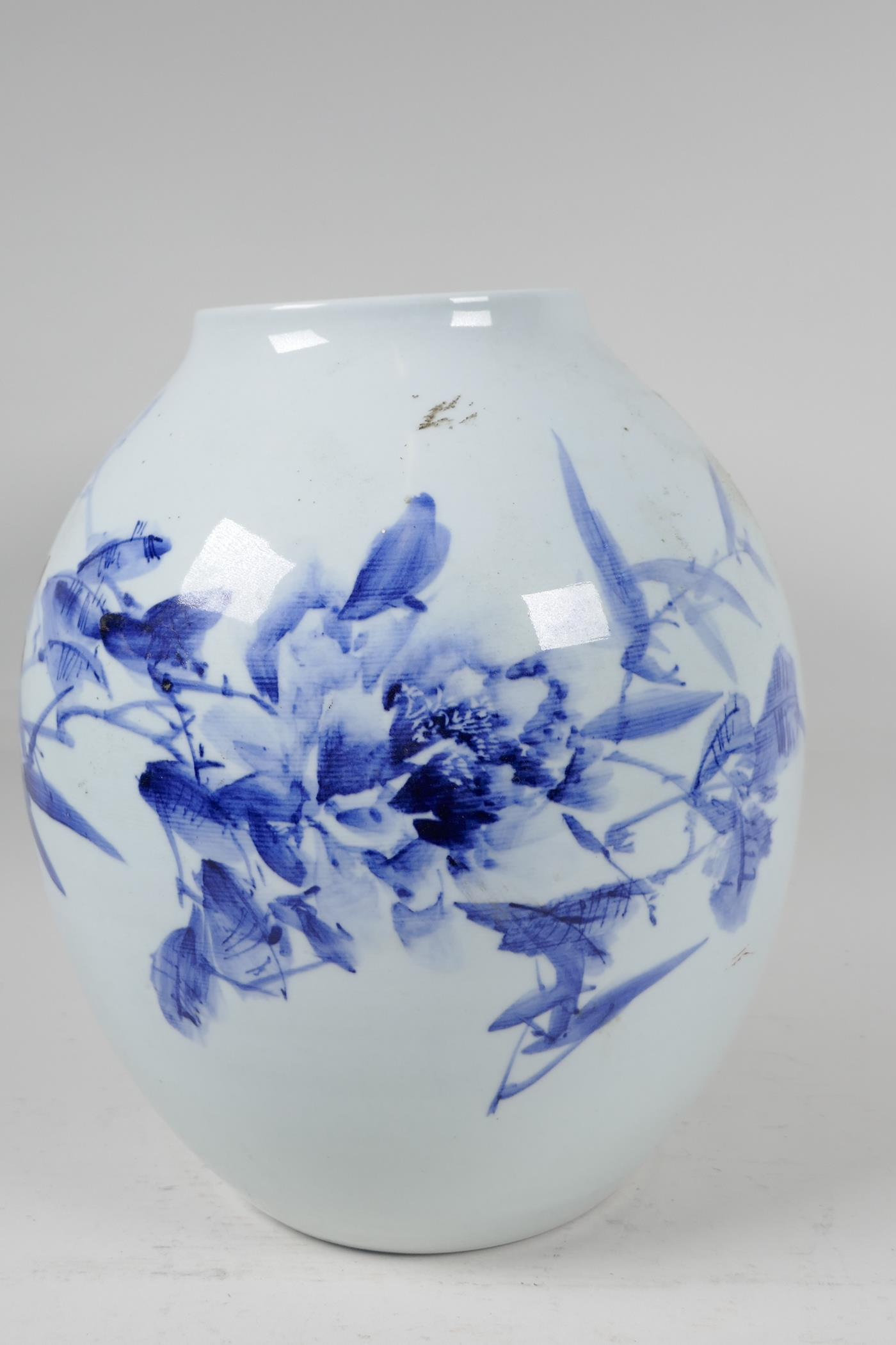 A Japanese porcelain vase decorated with stylised flowers in blue and red with character