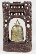 An oriental table gong with hardwood frame carved as dragons around a pagoda, with bell shaped gong,