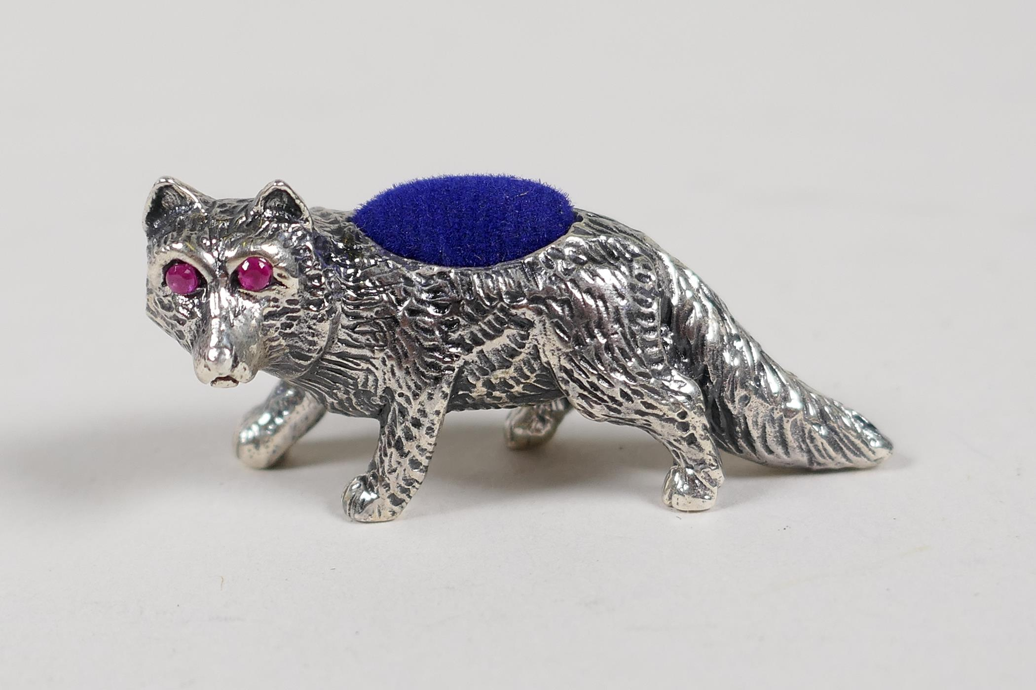 """A sterling silver pincushion in the form of a fox set with ruby eyes, 1½"""" long"""