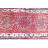 "A full pile red ground hand woven Persian Heriz runner, small repair, 41"" x 131"""
