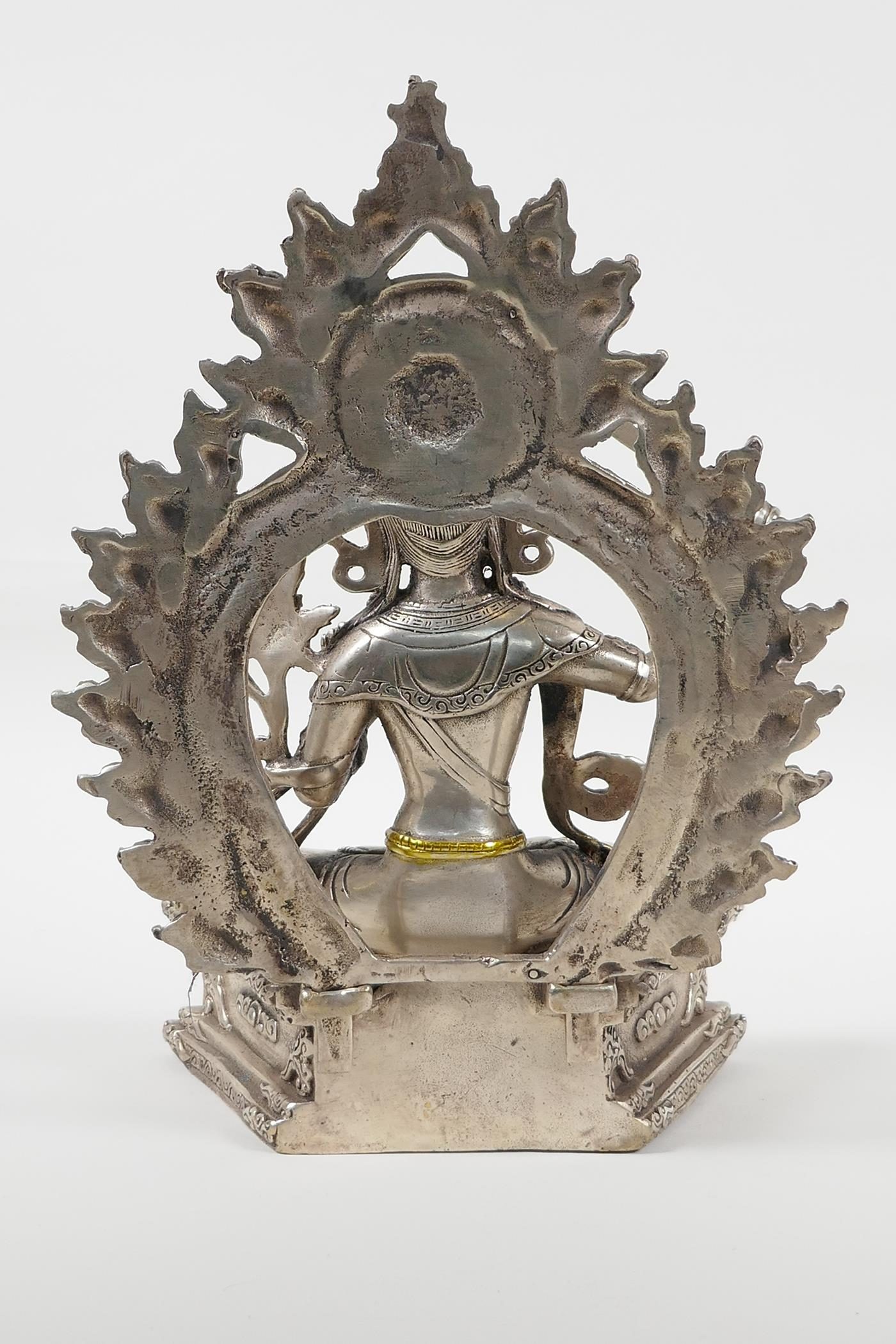 A Sino Tibetan white metal figure of a seated deity carrying a sword with gilt highlights, double - Image 3 of 5