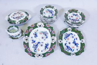 A Masons ironstone part dinner service decorated with Imari style flowers within a green border,